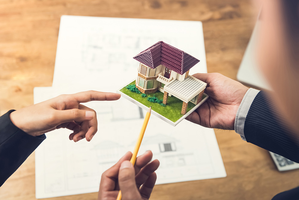 Housing developer agent holding an architectural model and explaining concept to client or architect for real estate development.